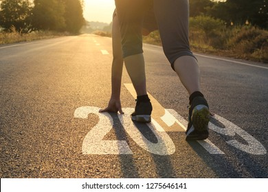 Healthy way of life new year concept. goals and plans, Healthcare and medical. Woman in sports wear running start to goals new year 2019 on the road in sunset background.