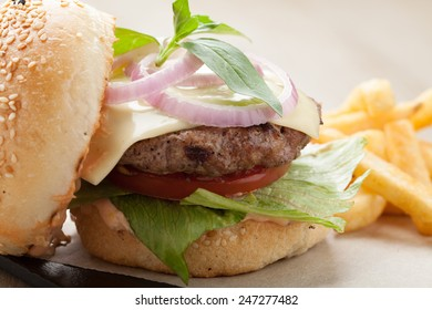 Healthy wheat sandwich burger with beef steak, cheese, tomato, lettuce, onion, basil, fried potato and ketchup  served for eating