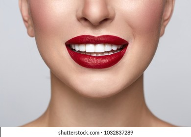 Healthy white smile close up. Beauty woman with perfect smile, lips and white teeth. Beautiful Model Girl with red lips and clear skin. Teeth whitening and cleaning, dental care.