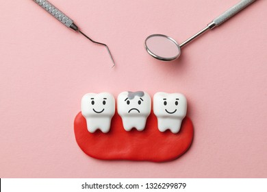 Healthy white teeth are smiling and tooth with caries is sad on pink background  and dentist tools mirror, hook.