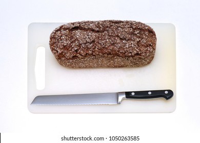 Healthy whole grain bread loaf on plastic board with knife for slicing on white background