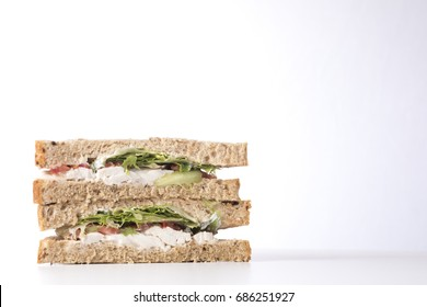 A healthy wholegrain bread chicken salad sandwich sliced into triangles and stacked on a plain white background with copy space.