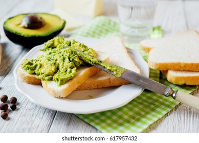 Healthy, wholesome and healthy breakfast or lunch, sandwiches with puree from fresh avocado with spices, mozzarella cheese and mineral water on a light rustic wooden background