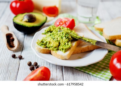 Healthy, wholesome and healthy breakfast or lunch, sandwiches with mashed potatoes from fresh avocado with spices, mozzarella cheese, tomato and mineral water on a light wooden background