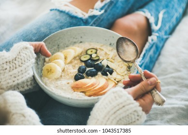 Healthy winter breakfast in bed. Woman in woolen sweater and shabby jeans eating vegan almond milk oatmeal porridge in bowl with berries, fruit and almonds. Clean eating, vegetarian food concept