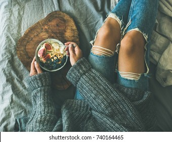 Healthy winter breakfast in bed. Woman in grey sweater and jeans eating rice coconut porridge with figs, berries, hazelnuts, top view. Clean eating, diet, vegetarian, vegan, comfort food concept
