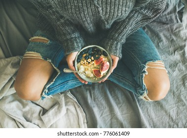 Healthy winter breakfast in bed. Woman in sweater and jeans holding rice coconut porridge with figs, berries, hazelnuts, top view. Clean eating, vegetarian, vegan, comfort food concept