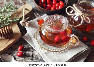 Healthy winter hot beverage. Rose hip tea in teapot, rosemary, honeyand berries