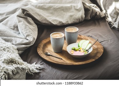Healthy winter  romantic breakfast in bed. Coffee, natural berry  yogurt with cereals, grapes and green apples on the rustic wooden board. Clean eating, eco diet, vegetarian food concept.