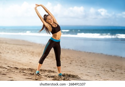 Healthy woman doing exercising on the beach, girl doing sport outdoor, happy female exercising, freedom, vacation, fitness and health care concept with copy space over natural background