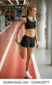 Healthy woman doing warmup exercise. Fit woman standing on red running track in gym and stretching leg