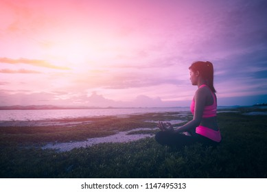 Healthy woman doing Yoga meditation exercises on beach in morning sunrise time.