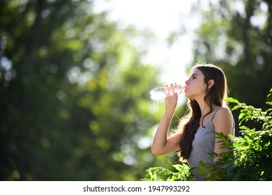 Healthy woman drinking water from bottle. Stay hydration concept. Unhidrated. Unity with nature, outdoor