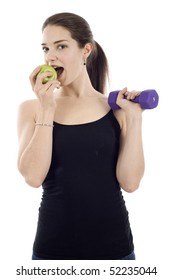 Healthy woman eating a green apple and holding a dumbbell isolated over white background