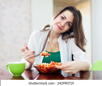 healthy woman eating veggie salad at home