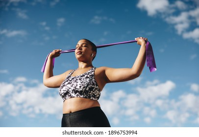 Healthy woman exercising with resistance band against sky. Female in sportswear doing resistance band workout outdoors in morning.