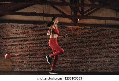 Healthy woman exercising with skipping rope at fitness studio. Sportswoman doing jumping rope workout at gym.