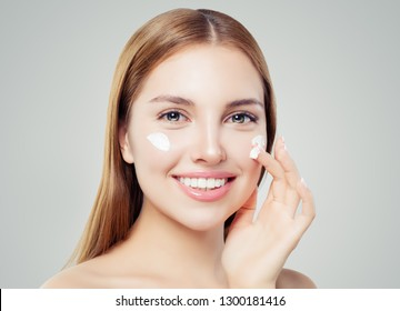 Healthy woman face. Cute girl with clear skin applying cream and smiling. Skincare, beauty and facial treatment concept