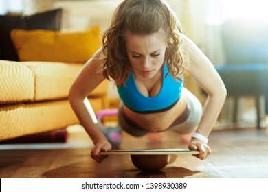 healthy woman in fitness clothes in the modern house doing pushups using balance board.