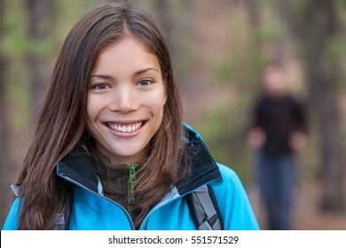 Healthy woman hiking outdoors. Happy young hiker girl walking in woods with group of friends. Smiling Chinese tourist.