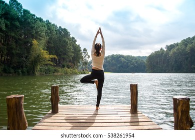 Healthy woman lifestyle active balanced practicing meditate and energy, mindfulness yoga on the bridge in morning the outdoor nature on the beach.  Healthy Concept.