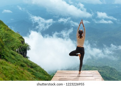 Healthy woman lifestyle balance pose exercising zen vital meditate and  practicing yoga at  the bridge in morning the nature mountain, nature background.  Healthy Sport Concept.