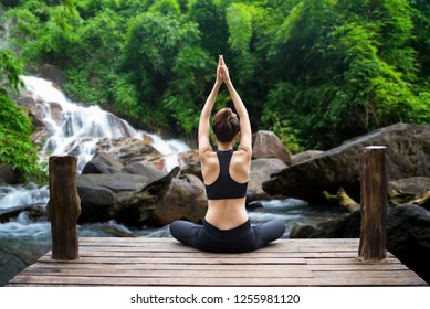 Healthy woman lifestyle balanced practicing meditate and zen energy yoga on the bridge in morning the waterfall in nature forest outdoors. Healthy life Concept.