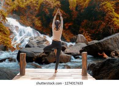 Healthy woman lifestyle balanced practicing meditate and zen energy yoga on the bridge in morning the autumn waterfall in outdoors nature. Healthy life Concept.