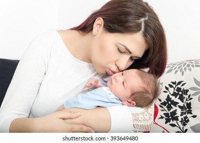 Healthy Woman and New Born Boy Relax in White Bedroom or Living Room. Nursery Interior. Happy Mother and Baby. Family at Home. Happy Child near to Mum. Newborn Child and Smiling Female Person.Domestic