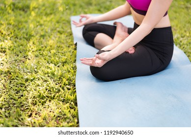 Healthy woman practicing yoga on the outdoor public park, yoga lotus pose.Healthy exercise lifestyle concept.