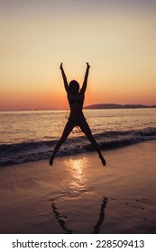 healthy woman practicing yoga on the beach at sunset