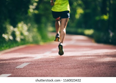 Healthy woman runner running on morning park road workout jogging