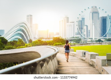 Healthy woman running exercise in Marina Bay barrage park at sunset time, singapore city, Singapore.