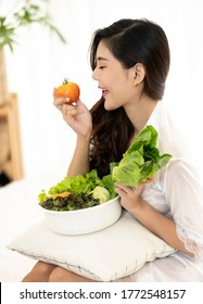 Healthy woman in sexy lingerie showing healthy salad vegetable on bed