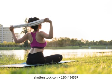 Healthy woman sitting on green glass for exercising and warming for practice yoga on the outdoor public park.Healthy exercise lifestyle concept.