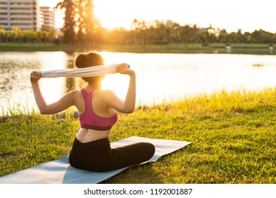Healthy woman sitting and white towel on green glass for exercising and warming for practice yoga on the outdoor public park with sun light.Healthy exercise lifestyle concept.