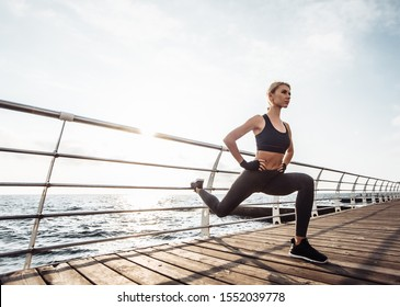 Healthy woman training on seaside promenade. Young attractive woman in sportswear does leg stretching before exercise on the beach at sunrise. Warm up