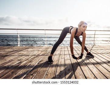 Healthy woman training on seaside promenade. Young attractive woman in sportswear does stretching before exercise on the beach at sunrise. Warm up