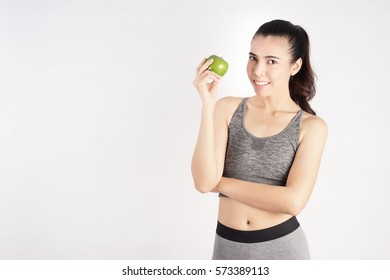 Healthy Woman in Workout Clothes holding an Apple Fruit, Fitness Girl in Workout Concept
