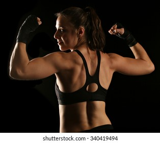 A healthy woman's back as she flexes with fist wraps