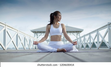 Healthy women practicing yoga. sitting in lotus pose meditation outdoors concentrating breathing asana yoga. beautiful landscape view and near sea on the bridge,  concept for exercising, health care