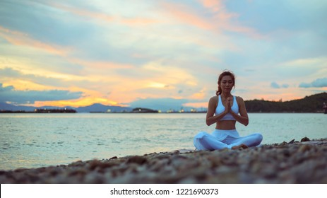 Healthy women practicing yoga. sitting in lotus pose meditation outdoors concentrating breathing asana yoga.Easy. landscape view sky on morning outdoor near sea, concept for exercising, health care