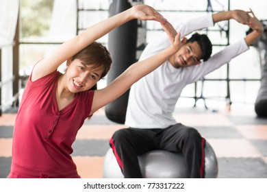 Healthy workout. Young cheerful woman sitting on the yoga mat and exercising with ball in the gym.