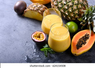 Healthy yellow smoothie with tropical fruits, pineapple, papaya and passion fruit, exotic vitamin drink