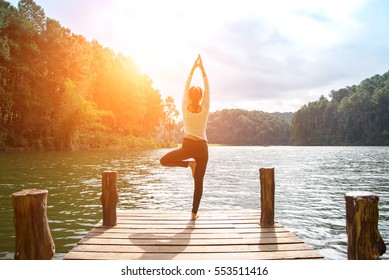 Healthy Yoga woman lifestyle balanced practicing meditate and energy yoga on the bridge in morning and sunset outdoors nature. Healthy Concept
