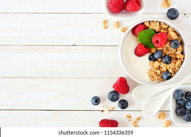 Healthy yogurt with raspberries, blueberries and granola. Above view, side border over a white wood background. Copy space.