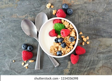 Healthy yogurt with raspberries, blueberries and granola. Top view scene over a dark background.