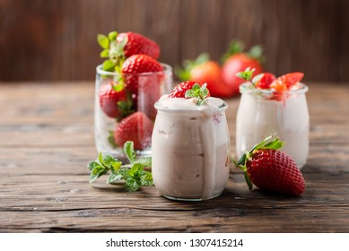 Healthy yougurt with stawberry and mint on the wooden table, selective focus