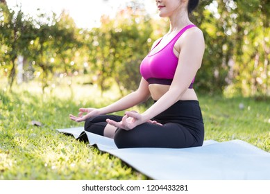 Healthy young Asian woman sitting on the mat and doing yoga lotus pose on green grass background in the outdoor public park.Healthy exercise lifestyle concept.