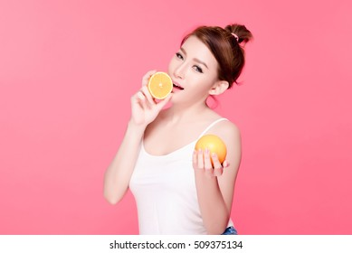 Healthy young beautiful woman holding and eating oranges, natural makeup. Oranges may boost your immune system and improve your skin. They also aid with heart health, cholesterol levels.